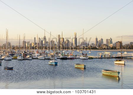 Yachts and boats in a marina with Melbourne's skyline