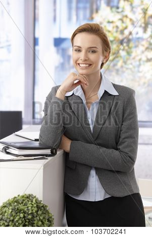 Beautiful young businesswoman smiling, looking at camera, leaning on counter.