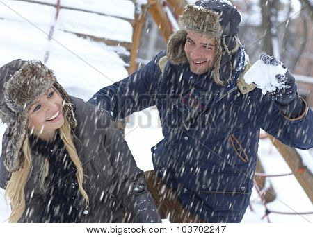 Outdoor photo of loving couple having fun at wintertime in snowfall.