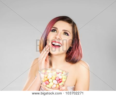 Attractive girl in dress with a bowl of sweets.