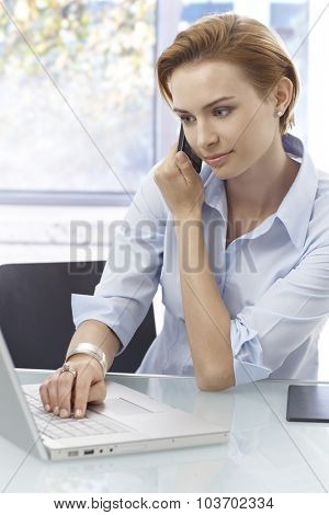 Young businesswoman sitting at desk, working on laptop computer, talking on mobilephone.