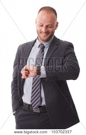 Businessman checking time on wristwatch, smiling happy.