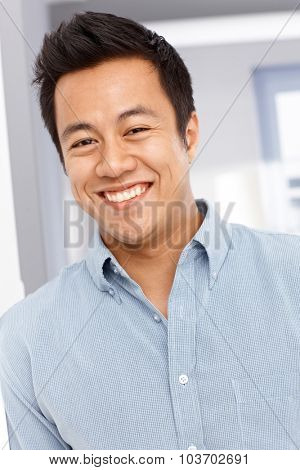 Close-up portrait of happy young Asian man, looking at camera.