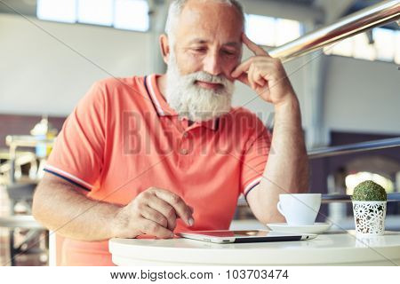 smiley senior man relaxing with cup of coffee and tablet pc in cafe. focus on the hand