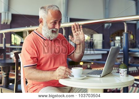 cheerful bearded man drinking coffee and having video chat with someone on the internet