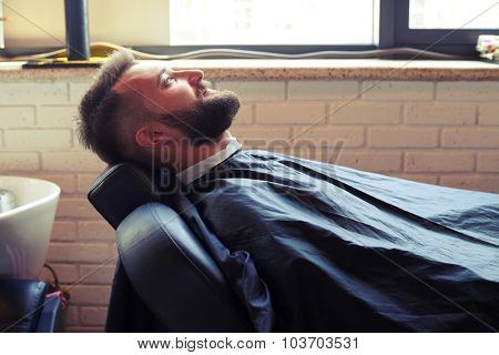 handsome man with beard sitting on chair in barbershop