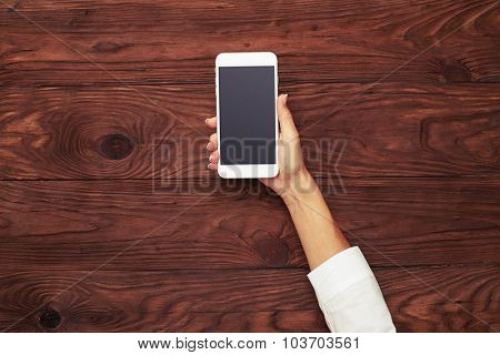 top view of womans hand with white smartphone over brown wooden background