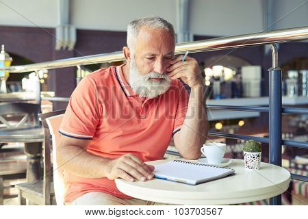 serious senior man holding pencil and looking at empty notepad in cafe