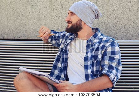 handsome bearded man with notebook sitting in bench at outdoor