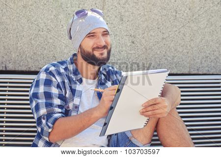 cheerful stylish man sitting on bench and holding white notepad