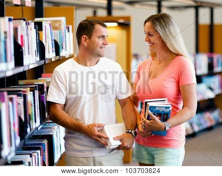 Couple standing in library with books
