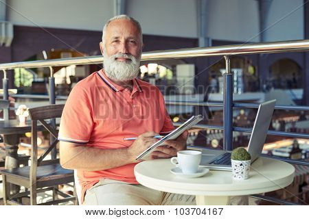 cheerful senior man holding pencil with notepad and looking at camera in cafe