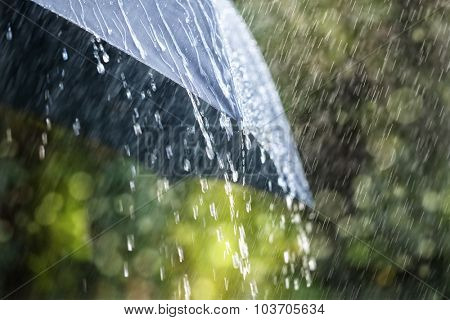Rain drops falling from a black umbrella concept for bad weather, winter or protection