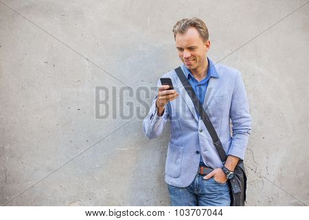 Man standing by the wall and looking at his telephone