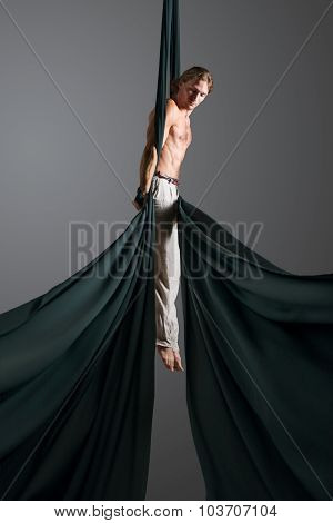 Sporty young man doing exercise with elastics aerial silk ribbons aerial