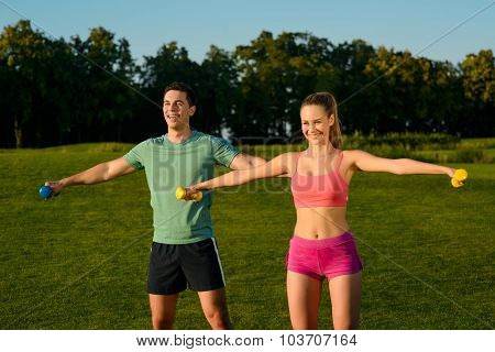 Guy with the girl shakes muscles  with dumbbells.