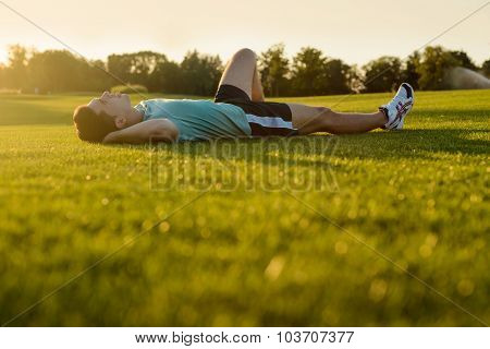 Guy lying in the park at sunset.