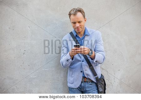 Man standing by the wall and using smartphone