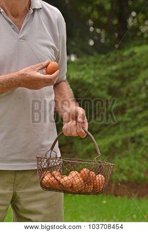 Happy farmer holding egg basket.