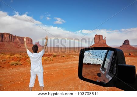 Monument Valley. Arizona, USA. The unique red sandstone buttes are reflected in the car mirror. The woman -  tourist threw up her hands in delight