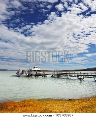 The lake in Argentina and tourist boat at the pier. Journey into a far country