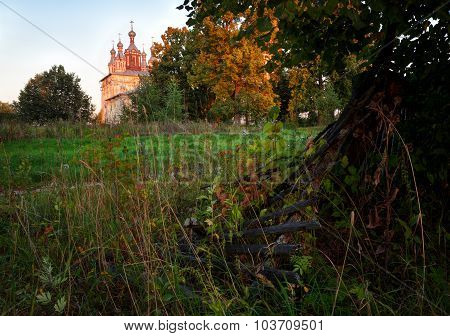 Rural Landscape With Old A Fence In The Foreground And Church In The Distance
