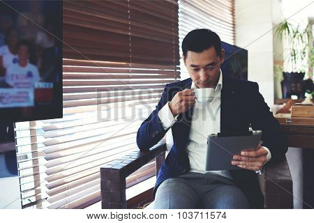 Confident businessman using touch pad for remote work while enjoying rest during coffee break