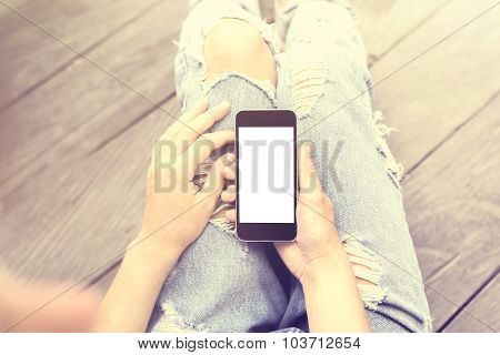 Girl Sitting On The Floor With A Blank Cell Phone