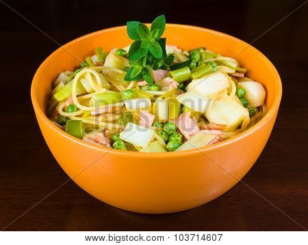 Bowl of healthy pasta with leeks, peas, bacon