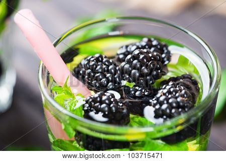 Cocktail with blackberry, lemon and mint in glass on a rustic wooden background