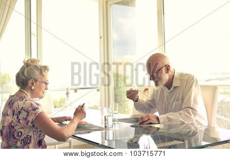 Elderly couple eating pasta