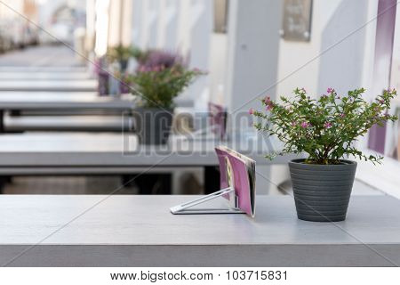 Outdoor Restaurant With Gray Tables And Pink Purple Flower Decoration