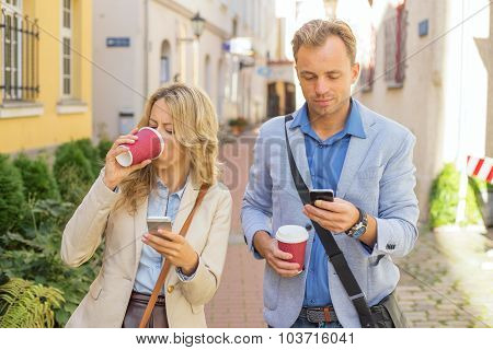 Man and woman using their smartphones