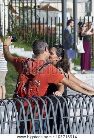Two Tourist Kissing While Making A Selfie