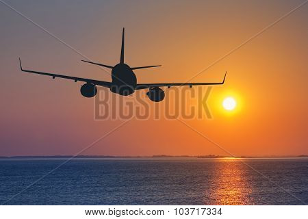 Silhouette Of Passenger Airplane Flying On Sunset