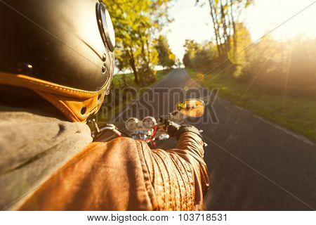Biker riding motorcycle  on road in morning sunny day. Shot from behind