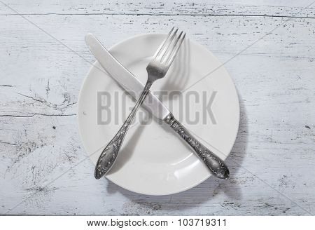 antique fork, knife and plate on white wooden table