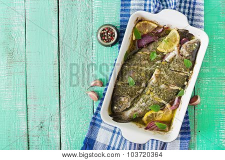 Baked trout  on a bright wooden background. Top view