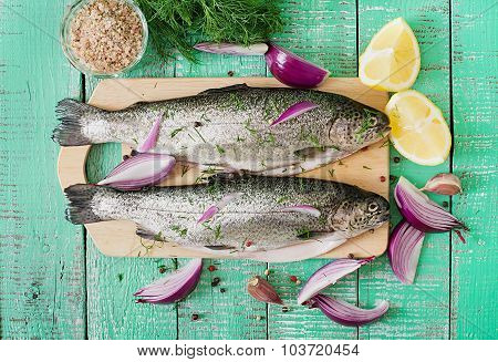 Gutted raw trout on a bright wooden background. Top view