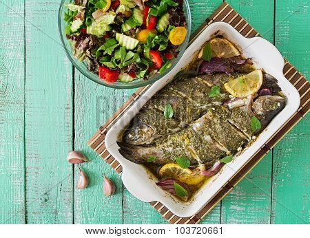 Baked trout and fresh salad on a bright wooden background. Top view