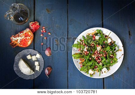 Rocket Salad With Cheese And Pomegranate On Rustic Wood, View From Above