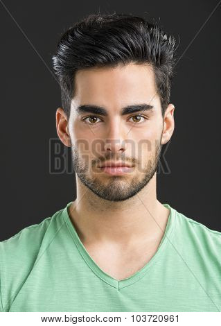 Portrait of handsome young man, isolated on gray background
