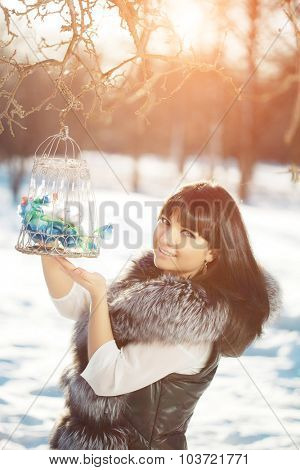 Young woman and birds in a cage in the winter forest Winter woman on background of winter landscape, sun. Fashion girl in forest wonderland. Winter sunset scene. Model in sunlight, backlight