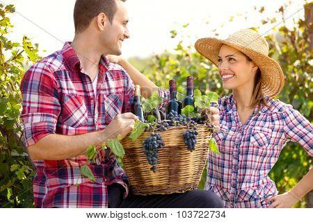 Couple of winegrowers holding full wicker basket in vineyard