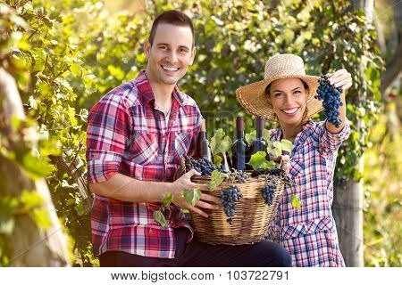 successful couple winegrower proudly show your wine and grapes