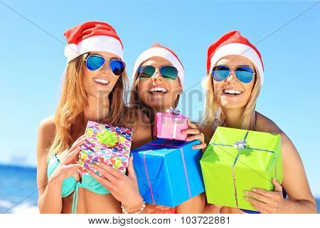 A picture of a group of women in bikini and Santa's hats holding presents on the beach