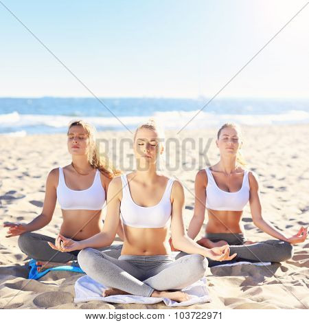 A picture of a group of women practising yoga on the beach
