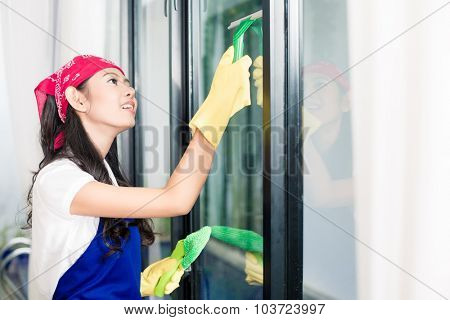 Asian woman cleaning windows in her home enjoying the chore