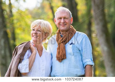 Senior couple of man and woman walking in autumn forest enjoying some leisure time together