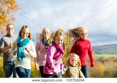 Girls running ahead at family walk through the park in fall or autumn